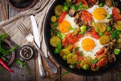 Déjeuner pour deux Oeufs au plat avec les légumes - shakshuka dans une poêle photographie stock