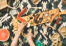 Déjeunez avec des casse-croûte et des mains de la femme coupant le fromage de brie Photo stock