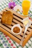 Déjeunez avec du beurre de pain grillé et la confiture et le jus d'orange avec l'orchidée de côté aiment le concept de petit déje Images stock