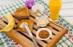 Déjeunez avec du beurre de pain grillé et la confiture et le jus d'orange avec l'orchidée de côté aiment le concept de petit déje Photo libre de droits