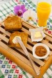 Déjeunez avec du beurre de pain grillé et la confiture et le jus d'orange avec l'orchidée de côté aiment le concept de petit déje Photos stock