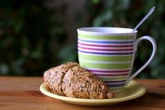 Déjeunez avec du café et le croissant frais sur la table en bois Fond brouillé Images stock