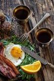 Déjeunez avec l'oeuf au plat et le becon dans le montant rustique photo stock