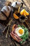 Déjeunez avec l'oeuf au plat et le becon de pot de café dans le montant rustique photo libre de droits