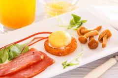 Déjeunez avec l'oeuf poché sur le pain grillé croustillant avec les champignons, le jambon et les verts Jus frais, sauce image libre de droits