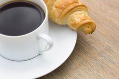 Déjeunez avec la tasse du café noir et du croissant Photographie stock libre de droits