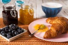 Déjeunez avec le croissant et les myrtilles au-dessus d'une nappe Photo libre de droits