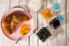 Déjeunez avec le croissant et les myrtilles au-dessus d'une table en bois Photos stock
