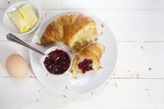 Déjeunez avec le croissant, l'oeuf rouge de confiture de fruit et le beurre sur un petit morceau Images stock