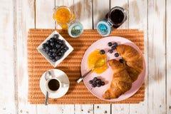 Déjeunez avec le croissant, les myrtilles, le café et la confiture au-dessus d'une étiquette Image libre de droits