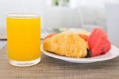 Déjeunez avec le jus d'orange, le croissant et les fruits Image stock