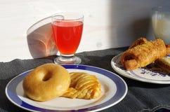 Déjeunez avec les butées toriques, le croissant salé, le jus de fruit et le lait Image stock