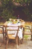 Déjeunez dans le jardin avec du vin et le fruit Dîner romantique en plein air Feuilles d'automne des fleurs Belle table scrapbook images libres de droits