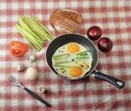 Déjeunez dans le style de village - oeufs au plat dans une poêle Image stock