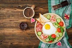Déjeunez le jour du ` s de Valentine - oeuf au plat sous forme de coeur, pains grillés, saucisse, lard et légumes frais Images stock