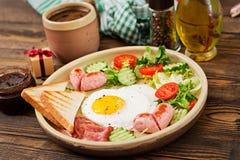Déjeunez le jour du ` s de Valentine - oeuf au plat sous forme de coeur, pains grillés, saucisse, lard et légumes frais Photo libre de droits