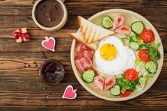 Déjeunez le jour du ` s de Valentine - oeuf au plat sous forme de coeur, pains grillés, saucisse, lard et légumes frais Photo stock