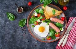 Déjeunez le jour du ` s de Valentine - oeufs au plat dans le coeur de forme, la saucisse, le pain grillé et la salade caprese Images libres de droits