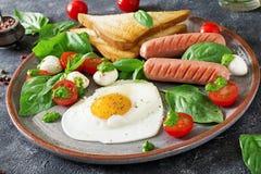 Déjeunez le jour du ` s de Valentine - oeufs au plat dans le coeur de forme, la saucisse, le pain grillé et la salade caprese Image stock