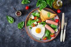Déjeunez le jour du ` s de Valentine - oeufs au plat dans le coeur de forme, la saucisse, le pain grillé et la salade caprese Images stock
