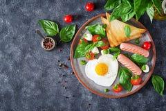 Déjeunez le jour du ` s de Valentine - oeufs au plat dans le coeur de forme, la saucisse, le pain grillé et la salade caprese Image libre de droits
