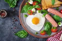Déjeunez le jour du ` s de Valentine - oeufs au plat dans le coeur de forme, la saucisse, le pain grillé et la salade caprese Photos libres de droits