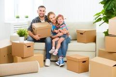 déménager à la maison neuf à enferme dans une boîte la famille de carton heureuse photo libre de droits
