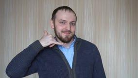 Déme una llamada El hombre joven del retrato que hace la demostración me llama muestra del gesto con la mano formada como el telé metrajes