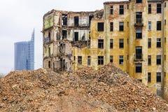 Démolition d'une grande vieille maison en pierre historique dans la ville, nouveaux bâtiments à plusiers étages à l'arrière-plan photo libre de droits