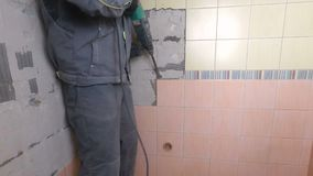 Démolition de vieilles tuiles avec le marteau piqueur Rénovation de vieux murs dans la salle de bains ou la cuisine clips vidéos