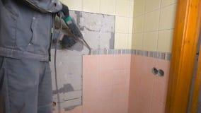 Démolition de vieilles tuiles avec le marteau piqueur Rénovation de vieux murs dans la salle de bains ou la cuisine banque de vidéos