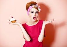 Dénommez la fille rousse avec le gâteau au fond rose. Photographie stock libre de droits