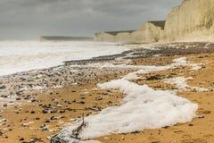 Dépôt de mousse de mer agitée sur la plage à Birling Gap, le Sussex pendant la tempête Desmond Photo libre de droits
