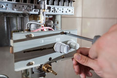 Dépanneur ajustant le chauffe-eau de gaz photographie stock libre de droits