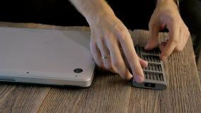 Dépanneur d'ordinateur portable travaillant avec un tournevis, sur la table un ordinateur portable et un ensemble de tournevis banque de vidéos