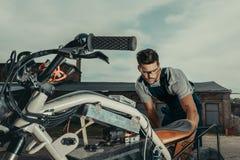 dépanneur dans les lunettes réparant l'extérieur debout de moto de vintage images libres de droits