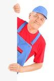 Dépanneur mûr souriant et posant derrière un panneau vide photos stock