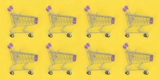 Dépendance de achat, amant de achat ou concept shopaholic Beaucoup de petits caddies vides exécutent un modèle sur un en pastel c images libres de droits
