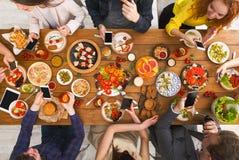 Dépendance de dispositif d'instrument, dîner d'amis avec des smarphones Photographie stock libre de droits
