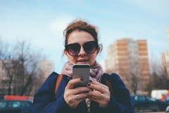 Dépendance sociale de media - le smartphone chez le ` s de la femme remet le service de mini-messages Photo stock