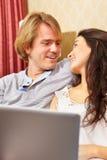 Dépense heureuse de couples avec l'ordinateur portatif Photo libre de droits