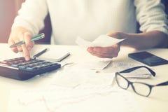 Dépenses de ménage - factures calculatrices de femme à la maison image stock