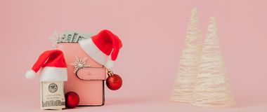 Dépenses de Noël Bourse en cuir rose avec le chapeau du père noël, le cadeau, l'arbre de sapin et les dollars de billets de banqu photo stock