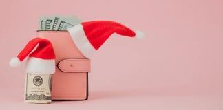 Dépenses de Noël Bourse en cuir rose avec le chapeau du père noël, le cadeau, l'arbre de sapin et les dollars de billets de banqu images libres de droits