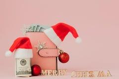 Dépenses de Noël Bourse en cuir rose avec le chapeau du père noël, le cadeau, l'arbre de sapin et les dollars de billets de banqu photos libres de droits
