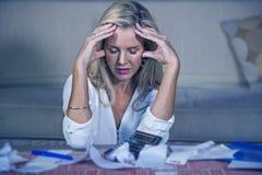 dépenses domestiques calculatrices attrayantes d'argent de femme blonde inquiétée et désespérée faisant la comptabilité d'effets  image libre de droits