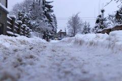 Dépiste dans la neige sur le village Je neige et personne qui nettoie les routes Chacun doit être soin photographie stock libre de droits