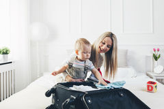 Déplacement avec des enfants La mère heureuse avec son emballage d'enfant vêtx pour des vacances Photographie stock libre de droits
