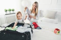 Déplacement avec des enfants La mère heureuse avec son emballage d'enfant vêtx pour des vacances Photo libre de droits