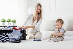 Déplacement avec des enfants La mère heureuse avec son emballage d'enfant vêtx pour des vacances Images stock